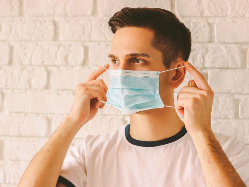 Homme mettant son masque chirurgical en le tenant par les élastiques.